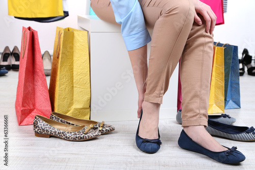 canvas print picture Young woman trying on shoes in shop