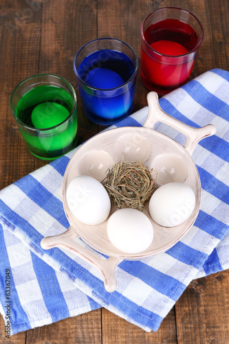 Eggs with liquid colour in glass on table close up
