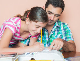 Hisdpanic father helping his daughter with her homework