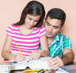 Hispanic father studying with his young daughter