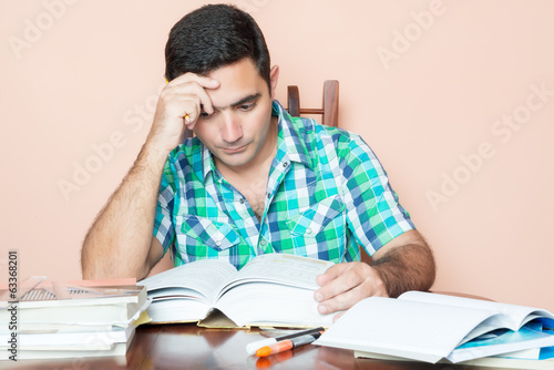 Adult hispanic man studying at home