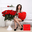 Beautiful Brunette Woman holding red heart over bouquet of roses