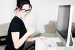 junge Frau mit Computer am Arbeitsplatz