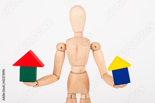 Small wood mannequin sit holding colourful block house isolated