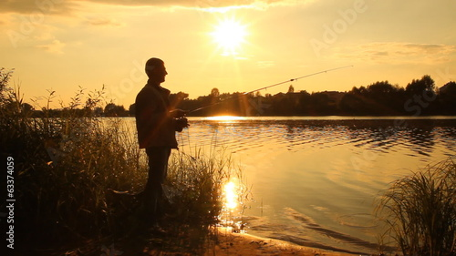 Man fishing. Fisherman. Sunset on the lake. summer landscape