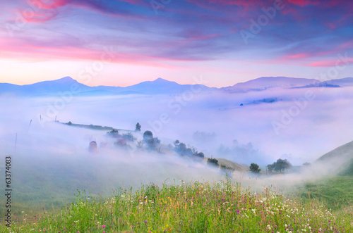 Panorama of the mountains and village in the morning mist. Summe