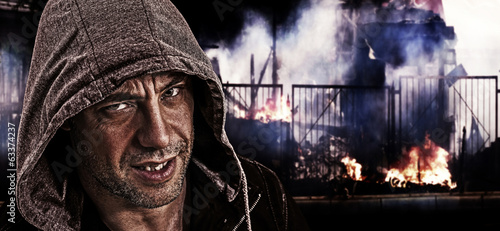 Scary evil man with hood on a background of street riots.
