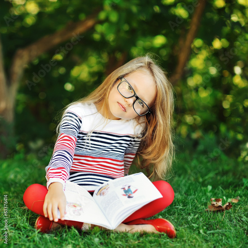 Adorable little girl with book in a summer park wearing glasses
