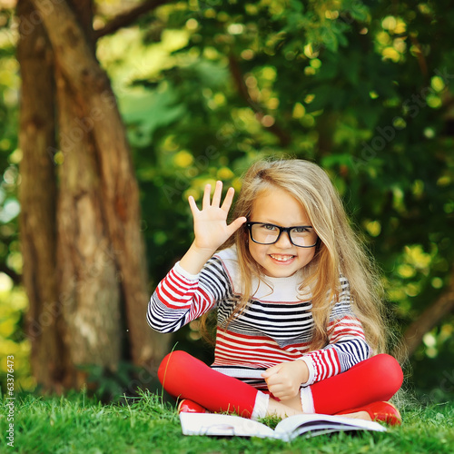 Cute little girl sits in a park. Reading book and hand gesture w