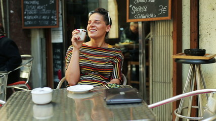 happy woman drinking coffee outside the cafe