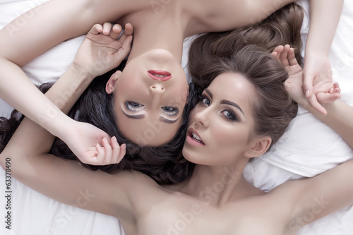 Portrait of seductive young women lying in bed