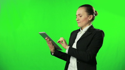 Businesswoman working on tablet computer against a green screen