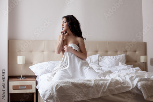 Shot of lovely model posing naked in hotel bedroom