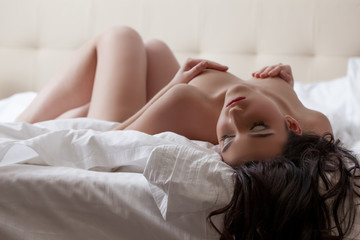 Sexy woman posing nude lying down with eyes closed