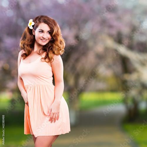 junge brünette Frau im Kleid vor blühenden Kirschbaum