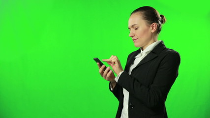 Woman dialing on her phone against a green background