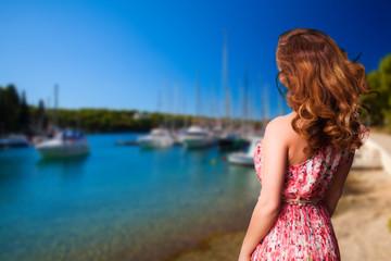 junge Frau im Sommerkleid vor Yachthafen-Szene