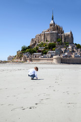 The boy plays on sand field against abbey St Michael