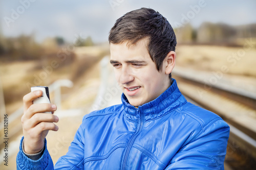 Teen with cell phone on the railway