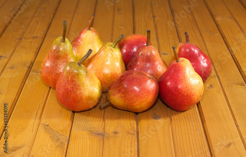 Many red and yellow pears lays on wooden desk closeup
