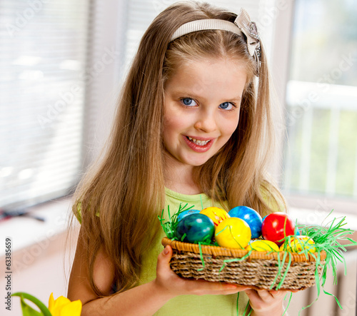 Children girl paint Easter eggs at home.