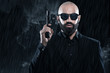 Dangerous bald gangster man with beard holding gun. Wearing blac