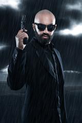 Dangerous bald gangster man with beard holding gun. Wearing blac