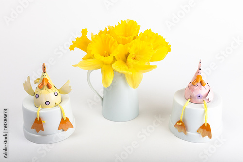Vase of daffodils with spring chickens