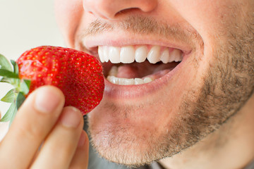 Closeup of man with beard biting a strawberry