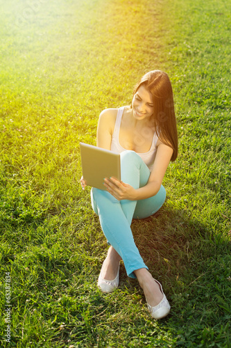 Beautiful young woman with tablet sitting on grass