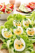Eggs with mayonnaise and vegetables on wood background