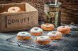 Closeup of falling powder sugar on fresh donuts