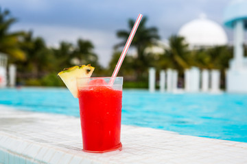 Glass of Strawberry Daiquiri cocktail next to a swimming pool