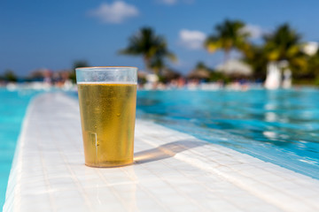 Glass of beer standing on the swimming pool ledge