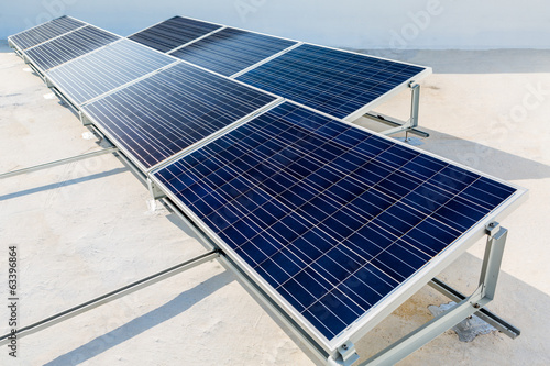 Solar panels standing on a rooftop under a bright sunny day