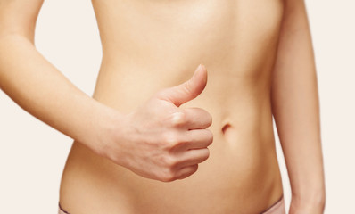 Woman is showing gesture thumb up in front of her abdomen