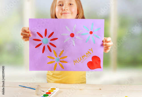 Happy girl holds greeting card