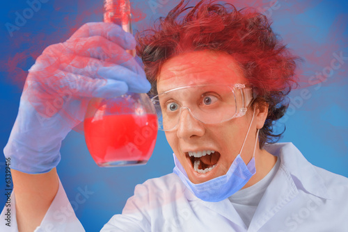 Scientist looks at flask with red liquid
