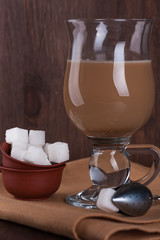 White sugar with a glass of coffee with milk