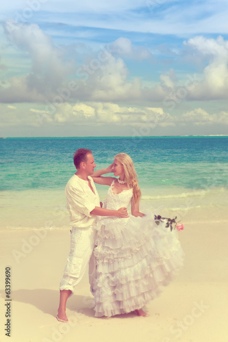 groom and  bride on the tropical beach.with a retro effect