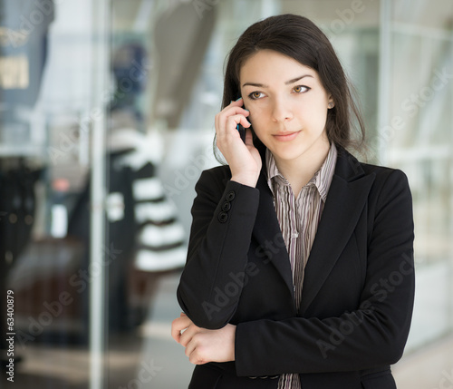 Brunette girl in coat speaking by phone. Selective focus.
