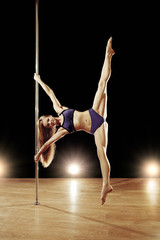 Young sexy pole dance woman doing splits