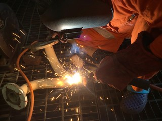 A man doing a welding on a steel pipe
