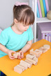 Little girl plays with construction blocks sitting at table in
