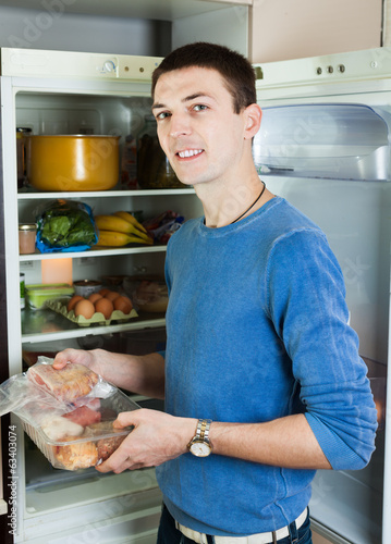 Handsome guy with meat near opened refrigerator