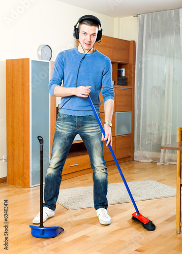 Happy guy   cleaning  in living room