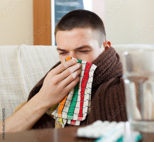 sick man in plaid uses handkerchief