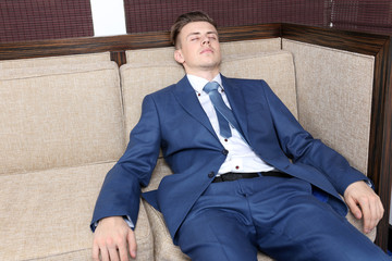 Young businessman resting on couch in office
