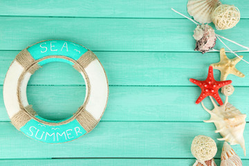 Lifebuoy and sea shells on wooden background