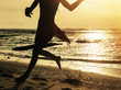 Silhouette of woman running along shore of ocean